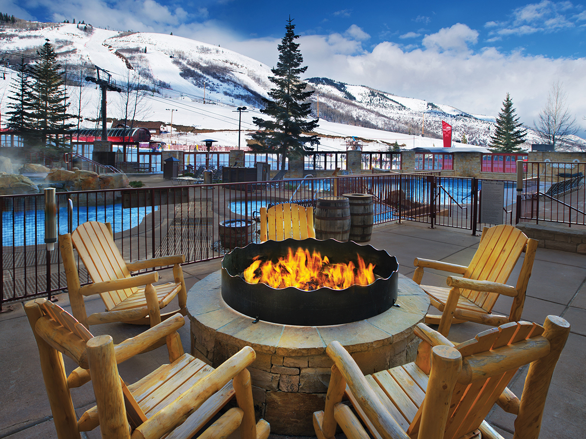 View of an outdoor fireplace with ski gondolas in the background.