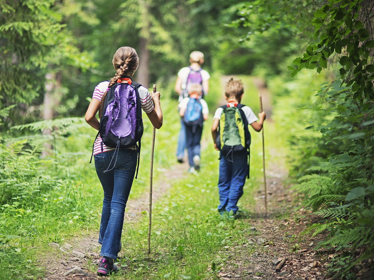 Mother and kids hiking along a pathway enjoying nature on an Adventure Travel experience.