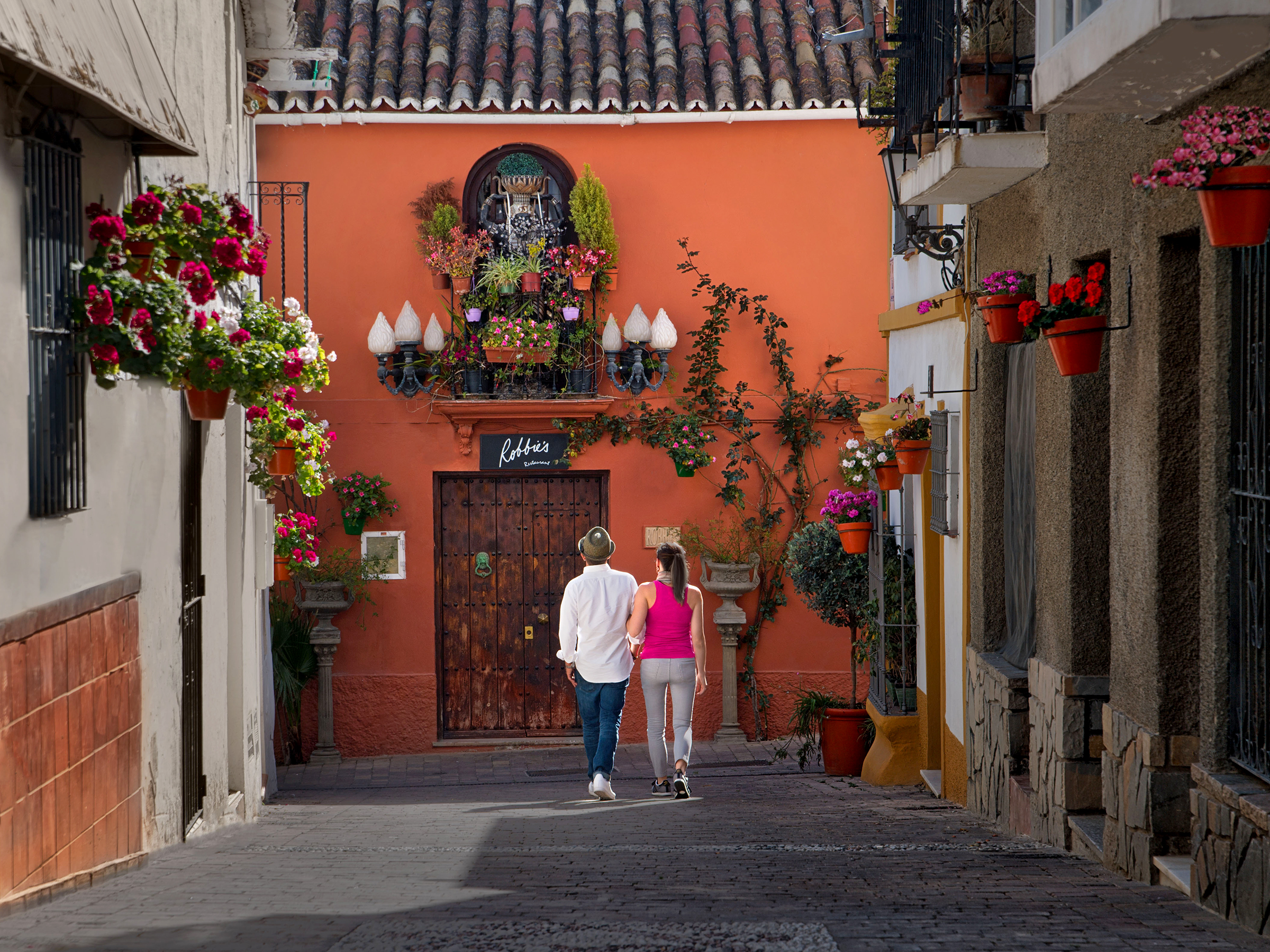 Couple walking down a corridor near Play Andaluza in Estepona, Spain.