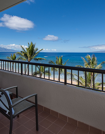 A villa balcony overlooking a beautiful beach with white clouds and blue sky.