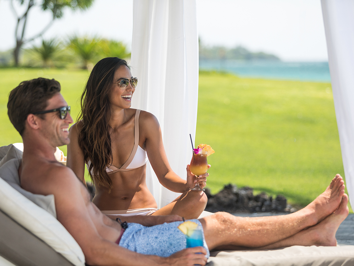 Couple relaxing in a cabana and enjoying tropical drinks.