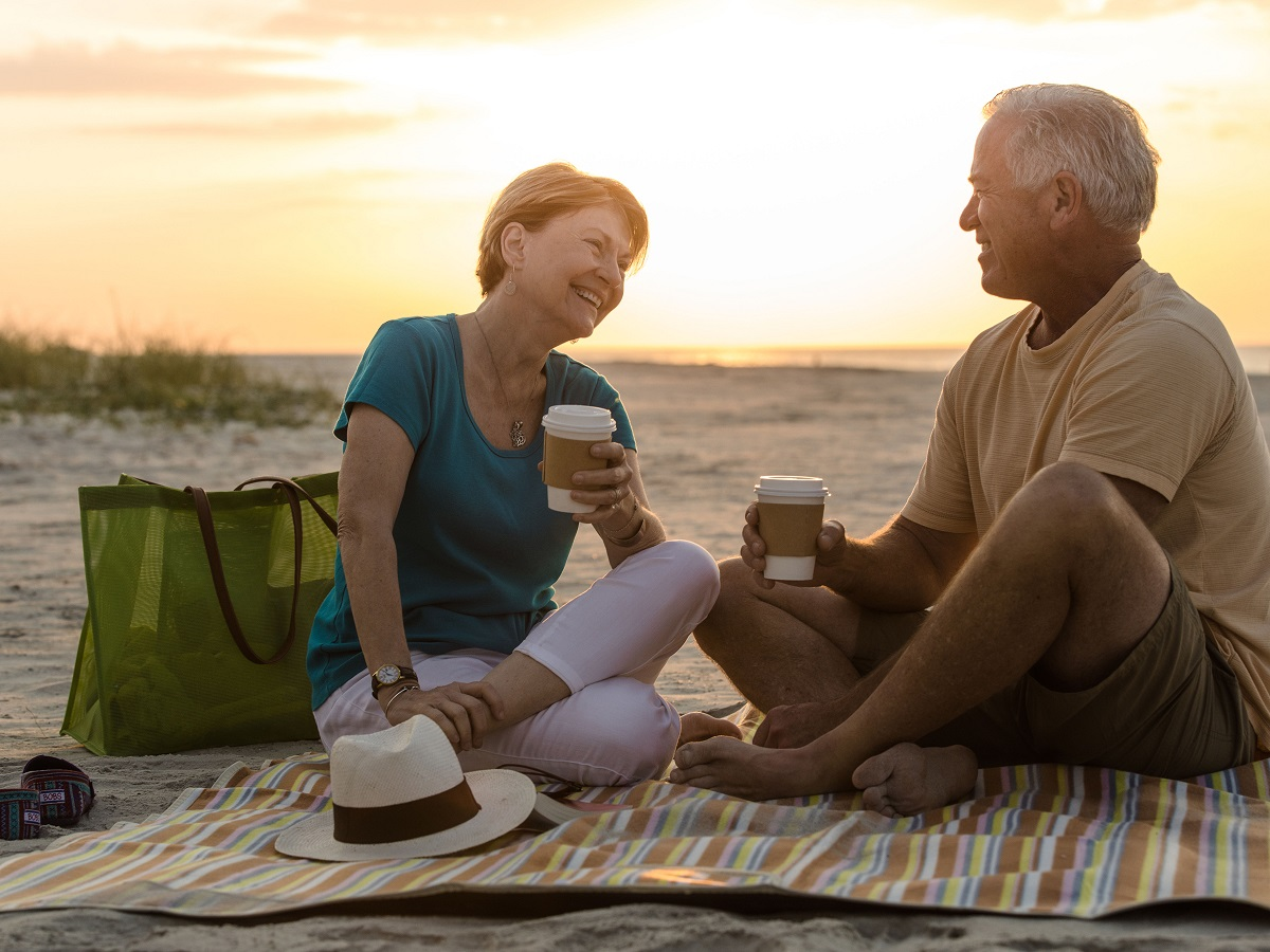 Senior couple having coffee picnic break on a beach vacation.