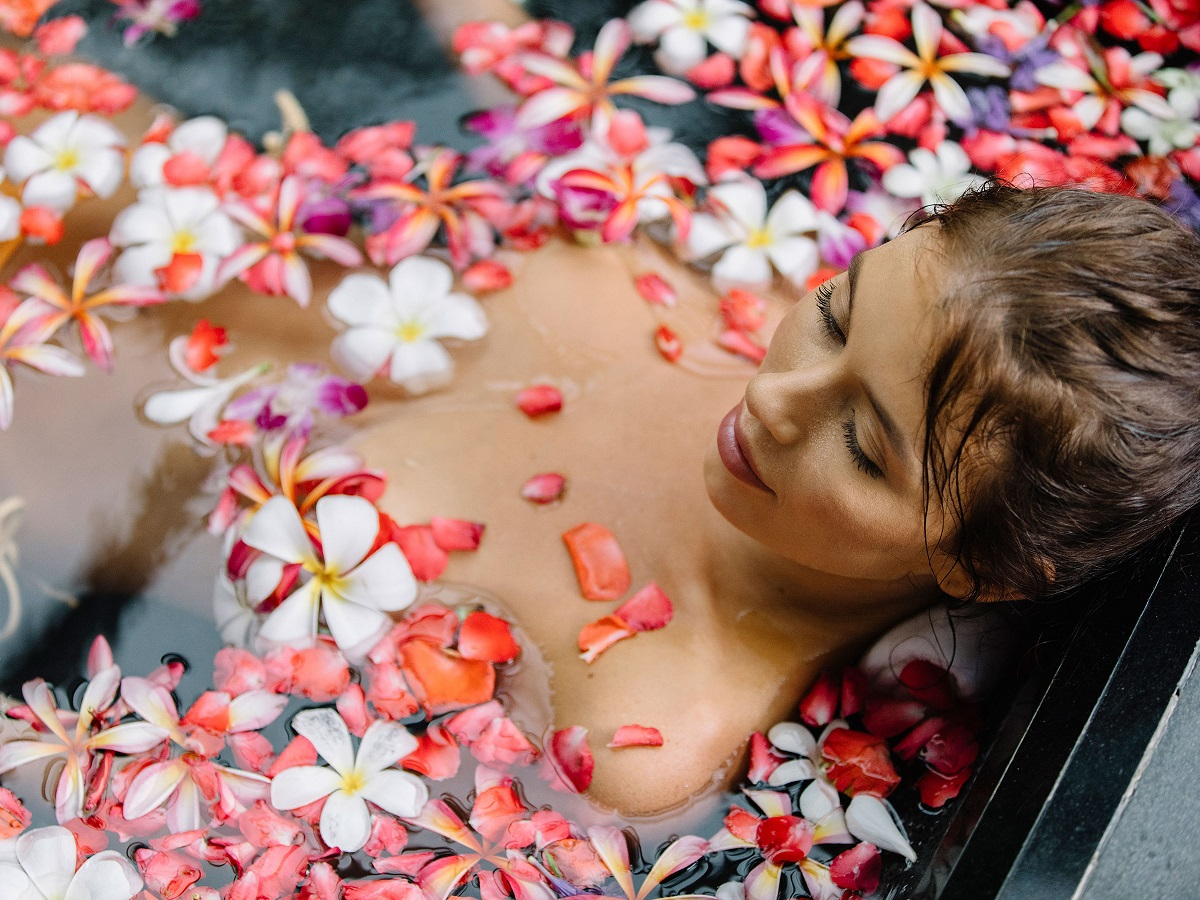 Woman relaxing a a pool of flowers.