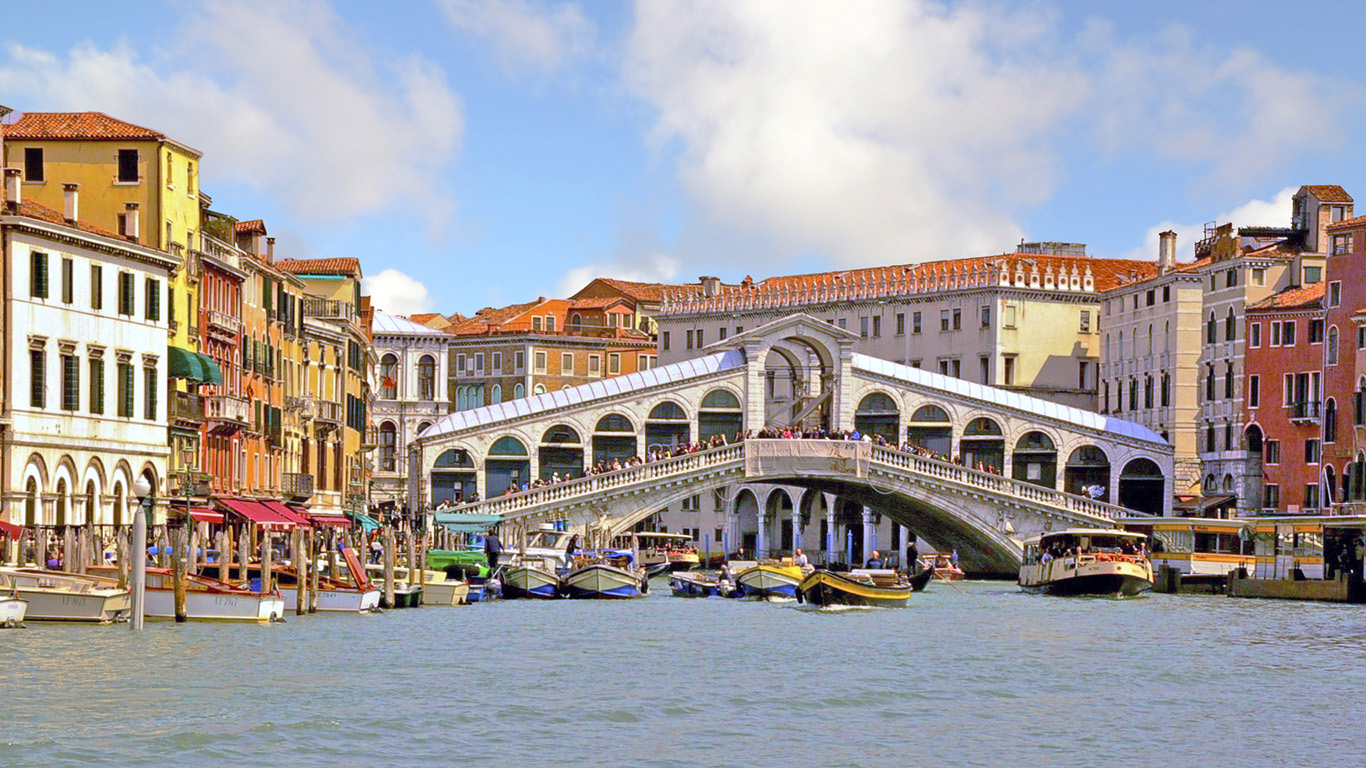 Revel in the magic of Italy. View of the Rialto Bridge along the Grand Canal in Venice.