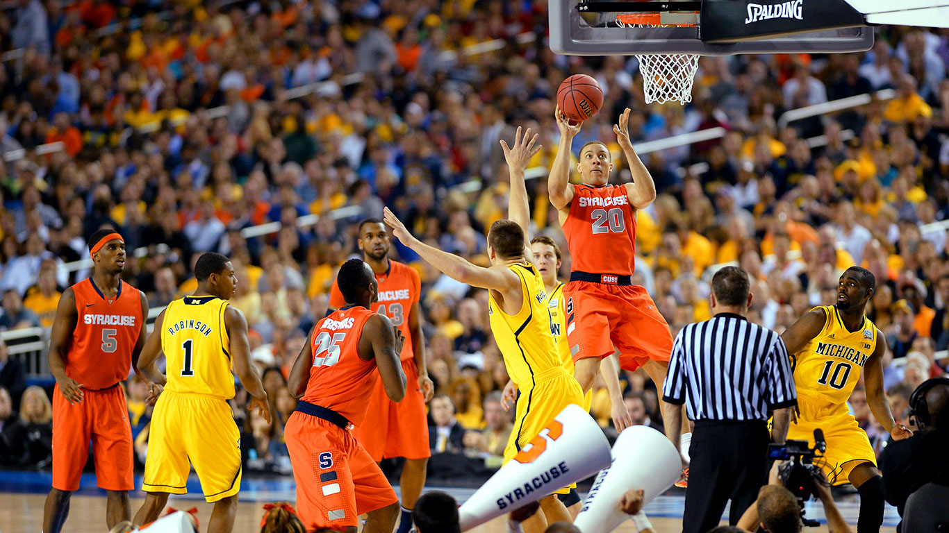 Michigan and Syracuse college basketball players face off in a NCAA game.