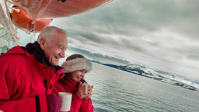 Couple admiring the scenery on their 8 Day Realm of the Polar Bear vacation package.