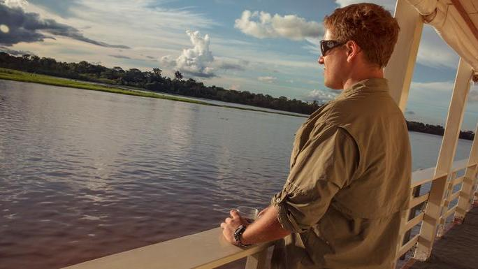 Traveler gazing out on a 7-day Amazon Riverboat adventure.